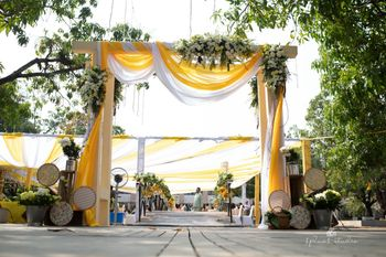 Rustic Entry decor with yellow and white drapes and floral arrangements