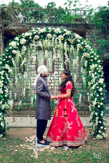 A couple holding hands infront of a giant floral wreath
