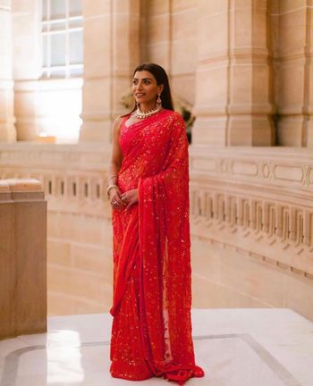 A friend of the bride in a sheer red saree