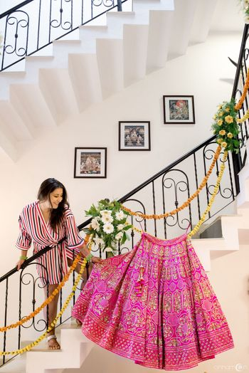 Bride getting ready shot with bright pink lehenga on hanger