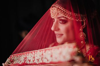 Bride holding her red dupatta as a veil