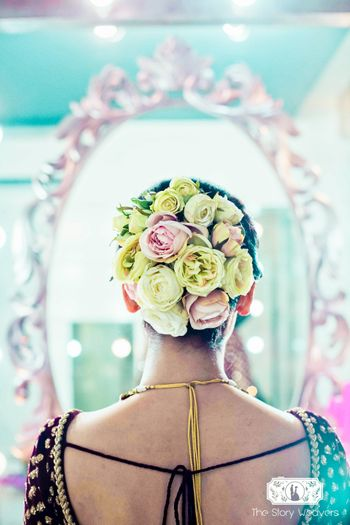 Unique bridal bun with big yellow and pink roses contrasting with dupatta