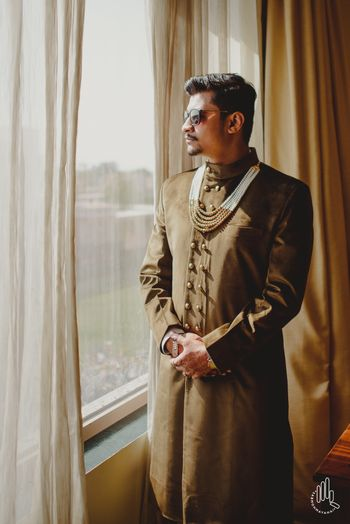 Groom in dull brown sherwani with double row of buttons and pearl necklace