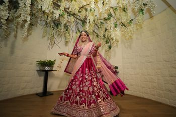 A happy bridal shot twirling in her beautiful wine coloured lehenga.