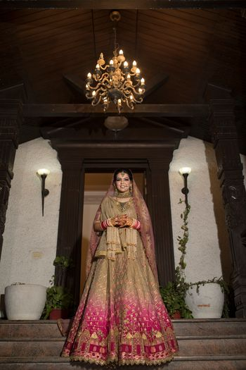 A beautiful bride in gold lehenga with a subtle mix of pink ombre in it.
