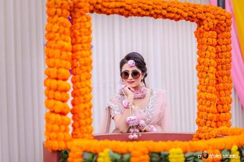 Bride on mehendi wearing sunglasses behind floral frame
