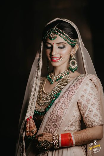 Contrasting unique bridal jewellery with green beads with pastel lehenga