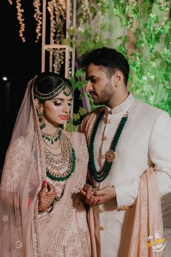 Pastel bride and groom outfits with dark green contrasting necklaces