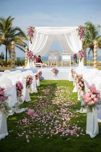 A white mandap setup with flowers and drapes