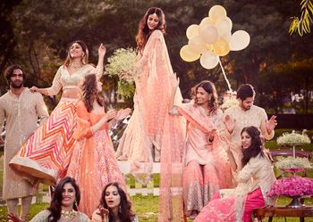 A bride and her bridesmaids in pastel outfits