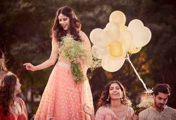 A bride in a shimmer, sequined lehenga with her bridesmaids