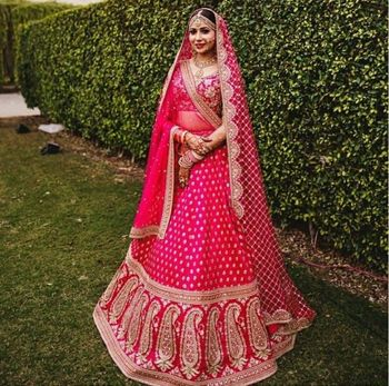 A bride in pink and gold lehenga with a double dupatta