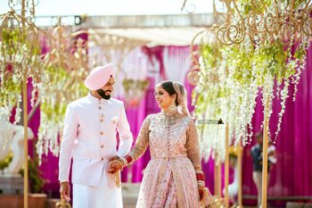 Coordinated sikh bride and groom wearing light pink outfits