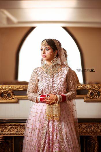 Bridal lehenga in light pink lehenga and gold kaleere