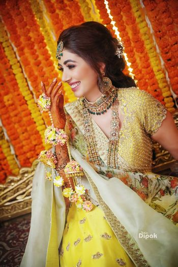 Photo of A bride-to-be wearing matching yellow floral kaleere with her yellow mehndi lehenga