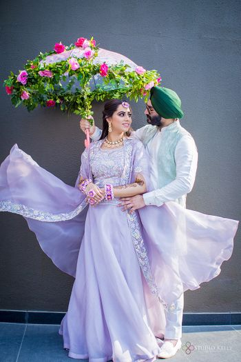 A couple pose with a floral umbrella on their mehndi
