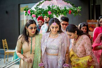 A bride in a lavender outfit and floral jewellery entering under a floral umbrella