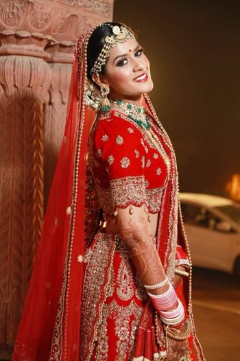 A beautiful bride on her wedding in a stunning red bridal lehenga and subtle makeup.
