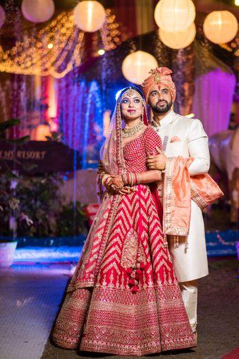 Contrasting bride and groom with bride in chevron lehenga