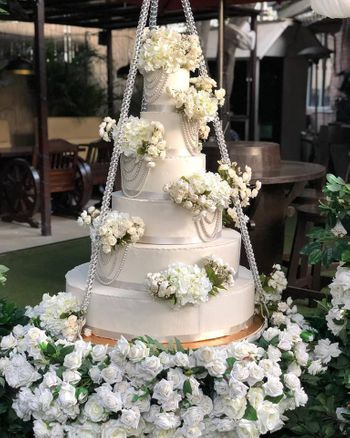 White wedding cake on a swing with florals