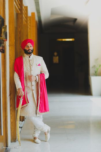 Photo of A groom in a stunning off-white embroidered sherwani coupled with bright pink dupatta and turban.