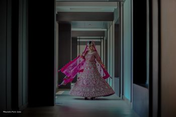 Twirling bridal shot in a stunning bright pink lehenga.