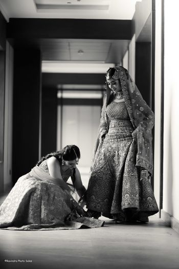 Bride getting help from her sister on her wedding day.