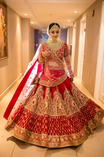 Photo of Bride in a heavy red and gold bridal lehenga