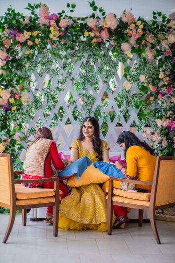 Bride getting her mehendi put against backdrop