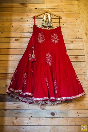 Red Lehenga and Gold Shoes on a Hanger