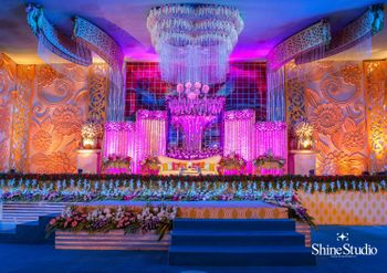 Elaborate stage decor for wedding in orange and purple