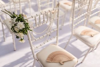 Summer wedding favour idea for guests with fans on chairs