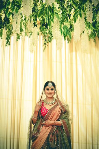 A bride in a multicolored lehenga with an oversized mangtikka