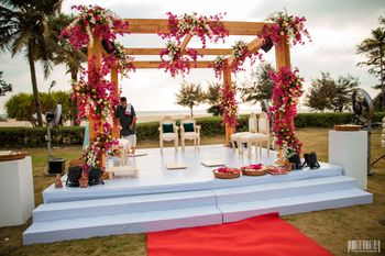 An open minimal mandap with pink flowers