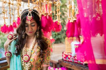 A bride in white and pink floral jewellery for her mehndi
