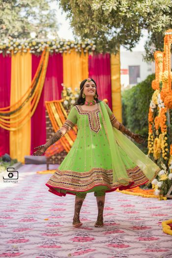A bride in a green mehndi outfit twirling in happiness