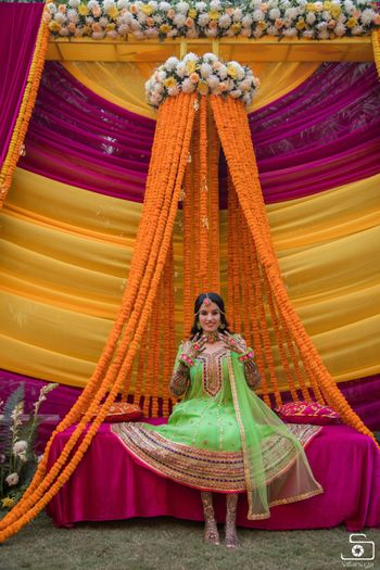 A bride in a parrot green mehndi outfit