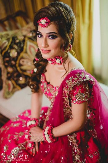 Bride in red lehenga and floral jewellery with off shoulder