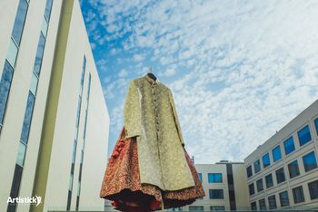 Photo of Lehenga and sherwani on hanger against the backdrop of the sky
