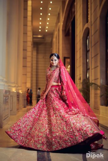Twirling bride shot in a red and gold lehenga