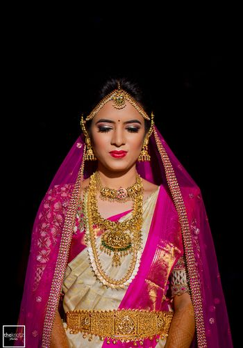Bride in white and pink wearing south indian temple jewellery