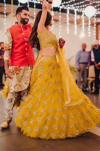 Dancing couple shot on sangeet with mustard yellow lehenga