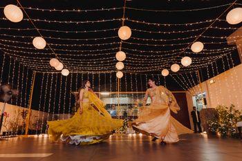 Bride and bridesmaid dancing in matching lehenga
