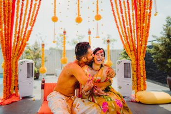 Fun couple haldi photo with couple kissing