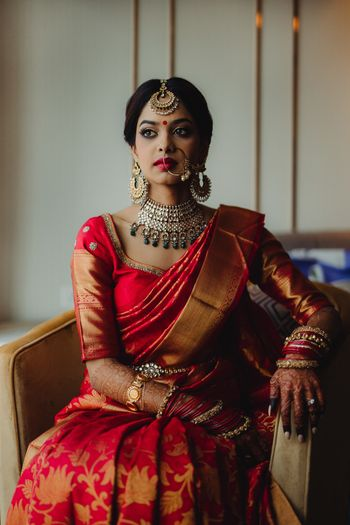 South indian bridal look in red kanjivaram and green jewellery