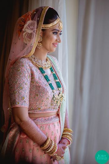 A bride in pink lehenga with contrasting jewellery