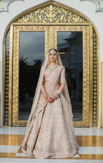 A bride in a blush pink lehenga on her wedding day