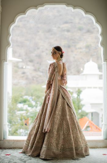 A bride in a light pink lehenga on her wedding day