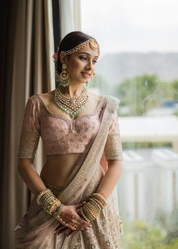 A  bride in a pink lehenga with contrasting green jewellery