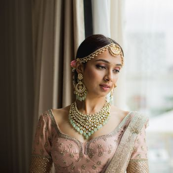 A bride in a pink blush outfit getting ready